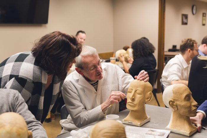Instructor showing a method to build facial features with model wax